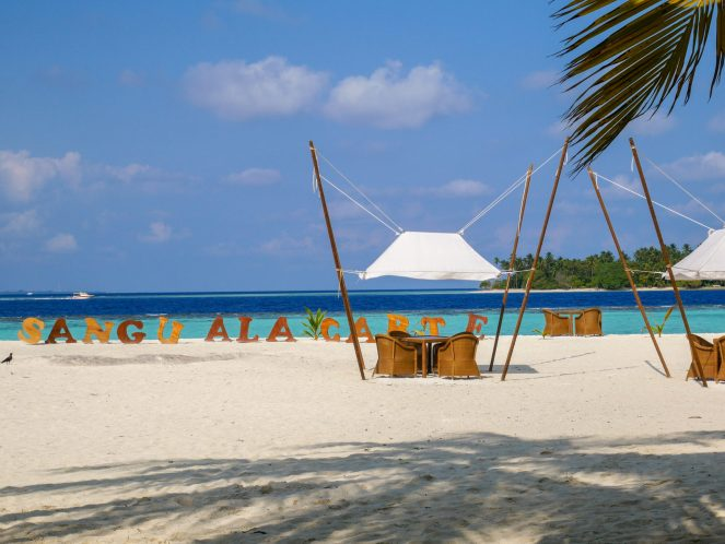 tables on the beach with a wooden Sangu à la carte sign on the beach at Kihaa Maldives
