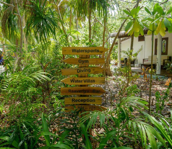 a wooden signpost to the facilities at Kihaa Maldives