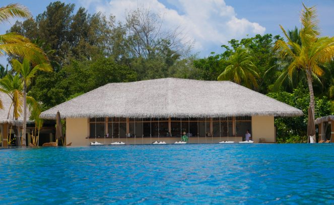 poolside bar with thatched roof at Kihaa Maldives