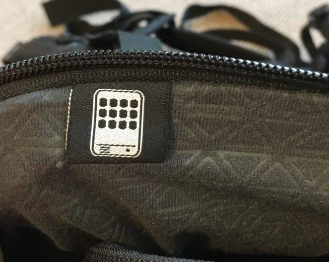A close up of the tablet pocket on a black Kathmandu Litehaul 38L Backpack