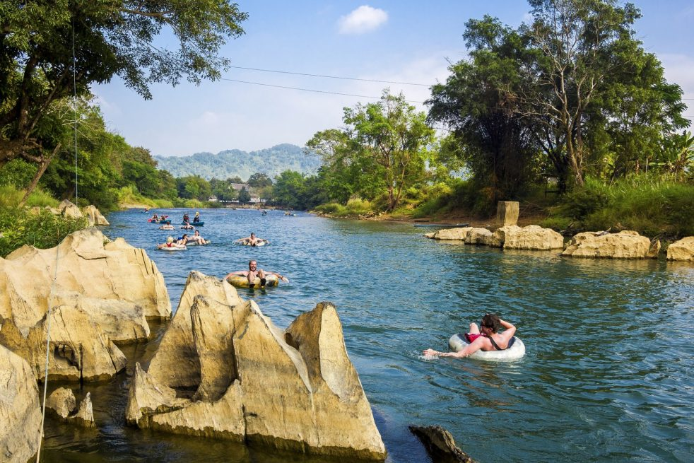 Tourists in rubber rings floating down the Nam Song River in Vang Vieng, Laos