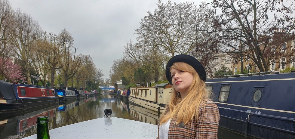 Rosie on a boat on the canal with canal boats and trees on either side