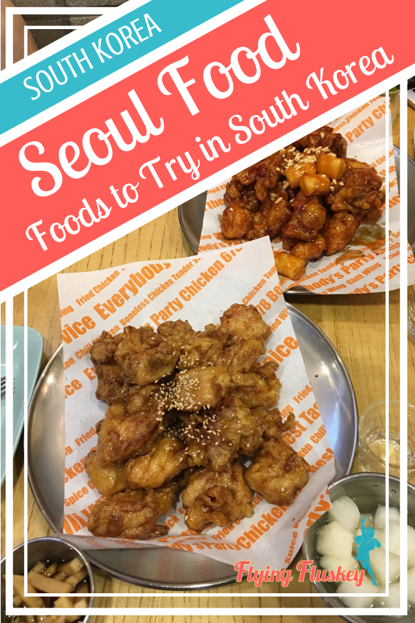 2 plates of Korean fried chicken and side dishes at Chicken 678. Top left a blue and red diagonal banner with white text reads 'South Korea. Seoul Food. Foods to try in South Korea'