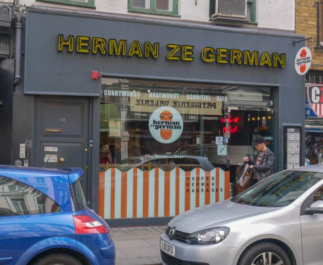 The grey front of a restaurant with Herman Ze German in yellow neon capital letters, Soho, London