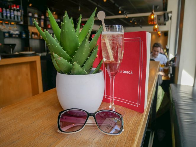 sunglasses a glass of prosecco in front of a cactus plant and a red menu at Obicà Mozzarella Bar, Soho, London