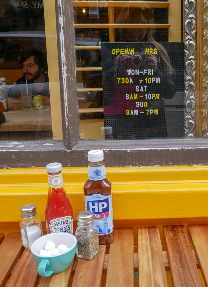 A wooden table with sauces, salt, pepper and cup of sugar cubes in front of an opening hours sign at The Breakfast Club, Soho, London