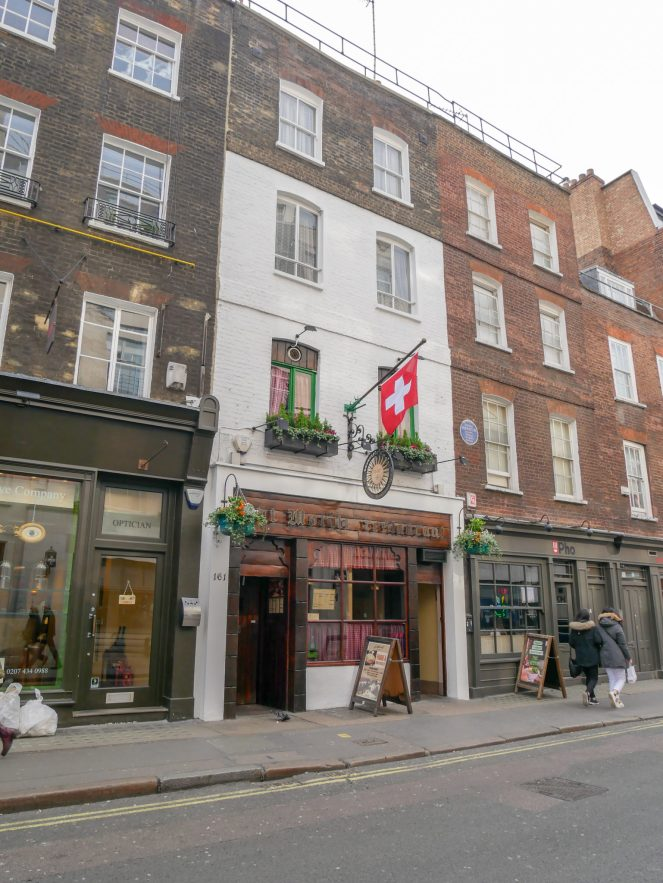 a small Swiss flag flies from a pole on the white wall above the wooden sign of St Moritz restaurant, Soho, London