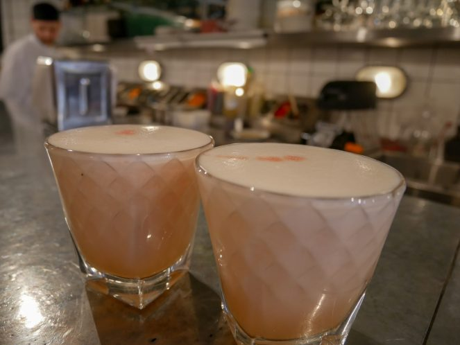 2 tumblers of pink pisco based foamy coctail on the counter in front of the open kitchen at Ceviche Peruvian restaurant, Soho, London