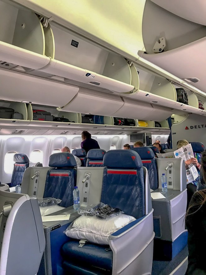Delta One seats and luggage bins on a Boeing 767 Delta Air Lines