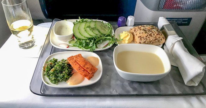 a champagne glass and a tray with plates of salad and cucumber, a bread roll and butter, parsnip and truffle soup and salmon tataki slices on Delta One Delta Air Lines