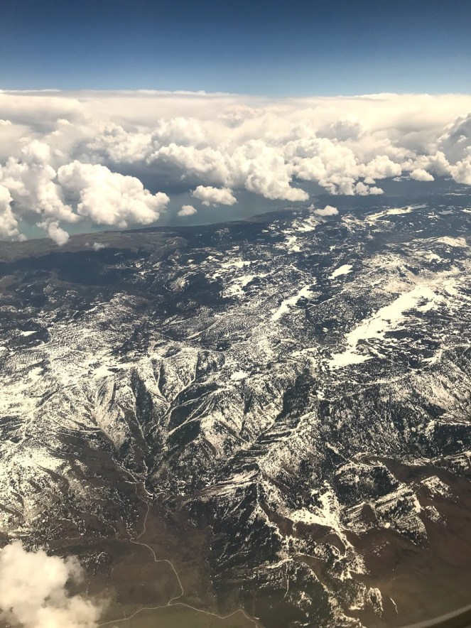 The snow capped Oquirrh Mountains surrounded by clouds, viewed form a plane