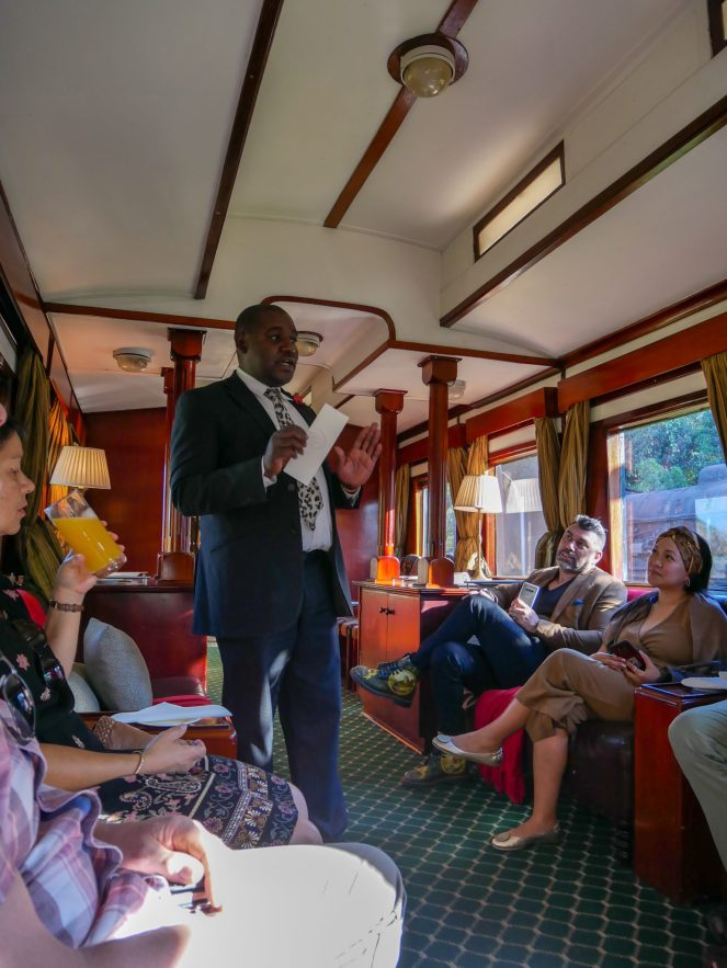 The host talks to guests in the Lounge Car of the Royal Livingstone Express train