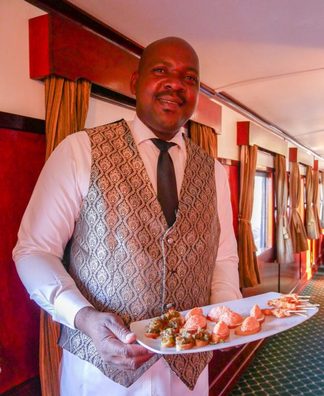The host wearing a patterned waistcoat, with a tray of canapes on the Royal Livingstone Express train