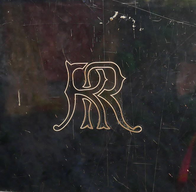 A gold Rovos Rail Logo on a black background on the Royal Livingstone Express train