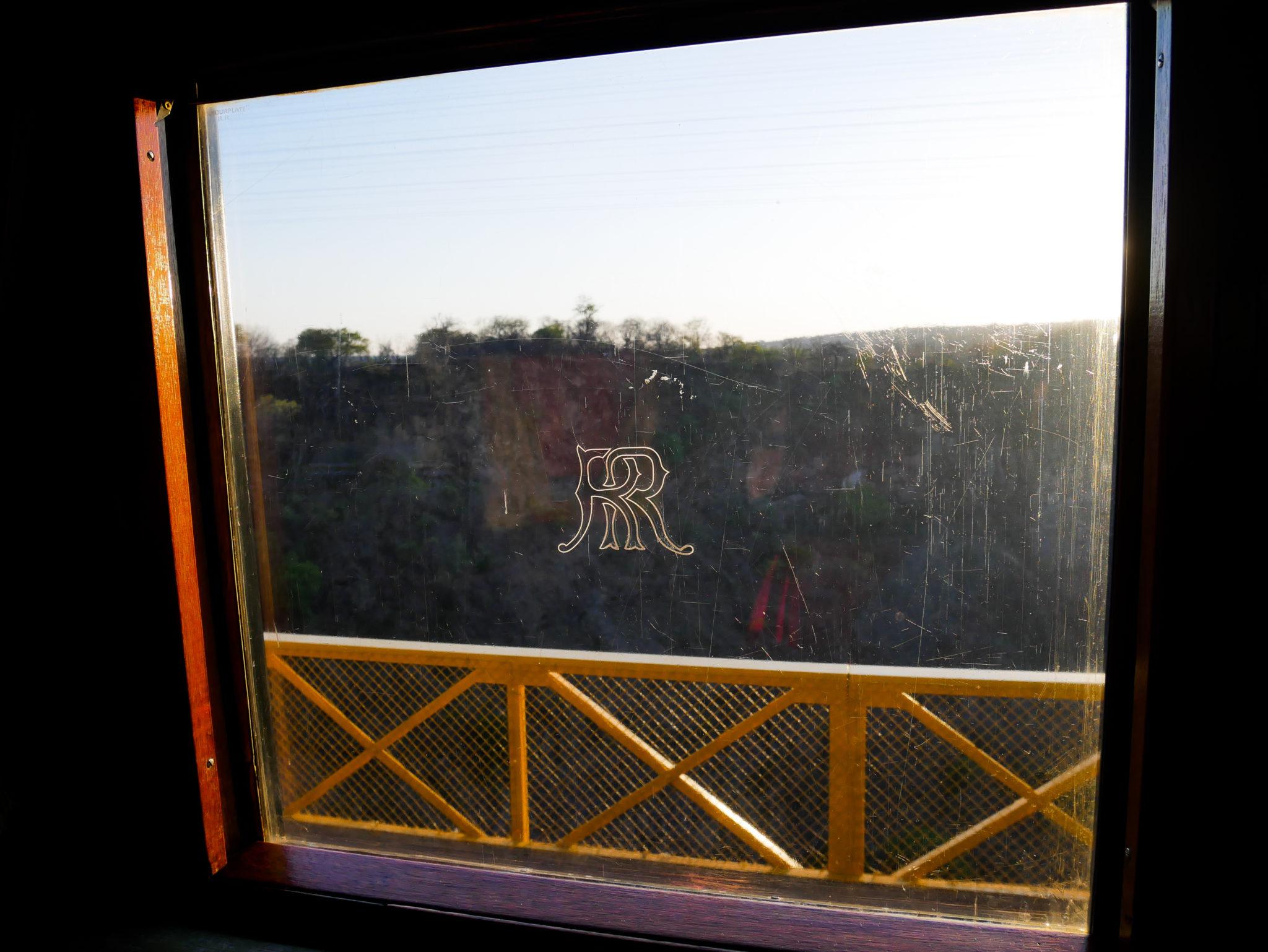 Evening sun shines through the Rovos Rail logo on the window of the Royal Livingstone Express train