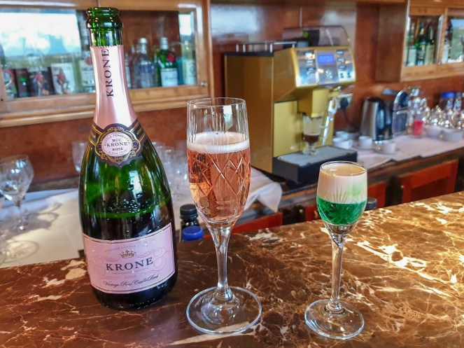 Krone Curvée Rosé Brut sparkling wine and a Springbok shot on the bar of the Lounge Car on The Blue Train