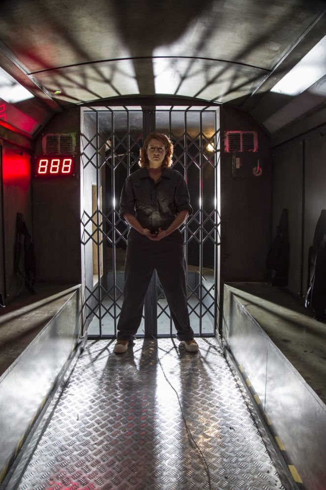 A woman blocks a metal doorway. She is wearing jumpsuit and looks a bit sinister.