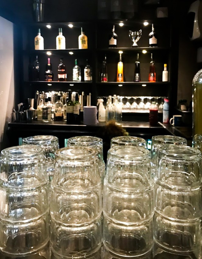 Glasses in the foreground with blurry bar bottles behind.