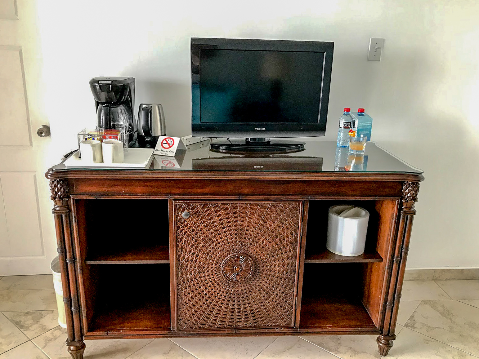 A big side table with intricatly carved wooden door on the front