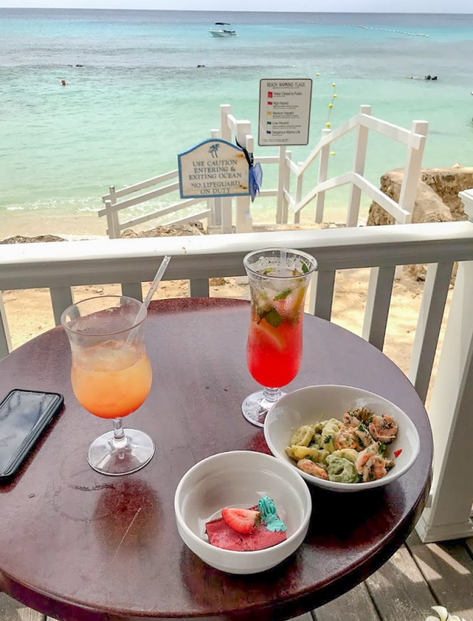 The sea is in the background with two brightly coloured cocktails and my sneaky buffet lunch on the table in front.
