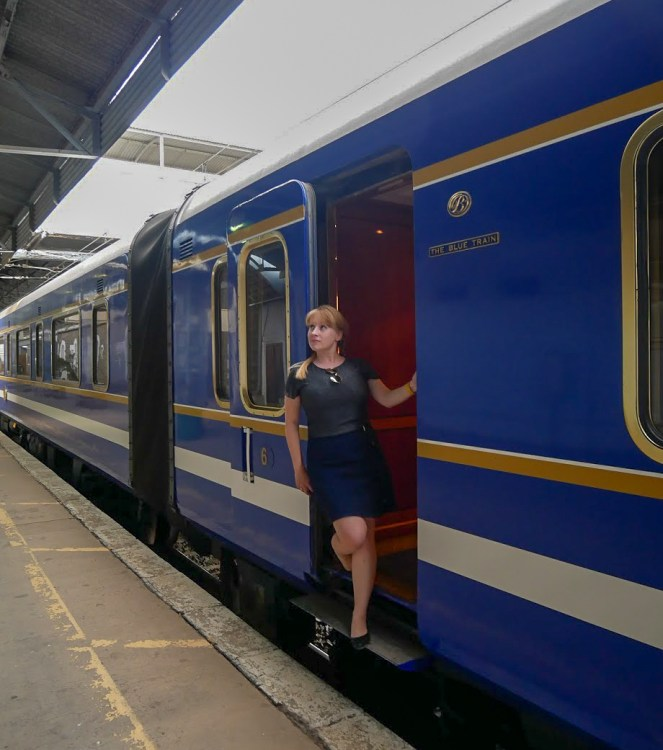 Rosie poses by the carriage door of the Blue Train in South Africa