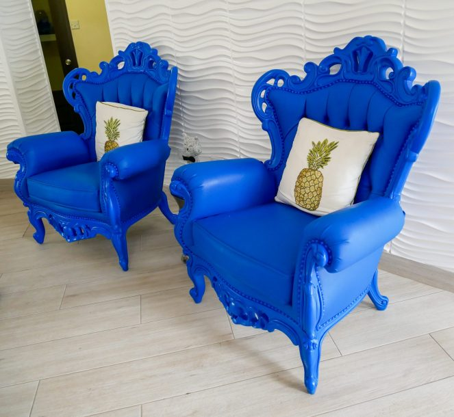 Two bright blue, versaille style chairs with pineapple cushions
