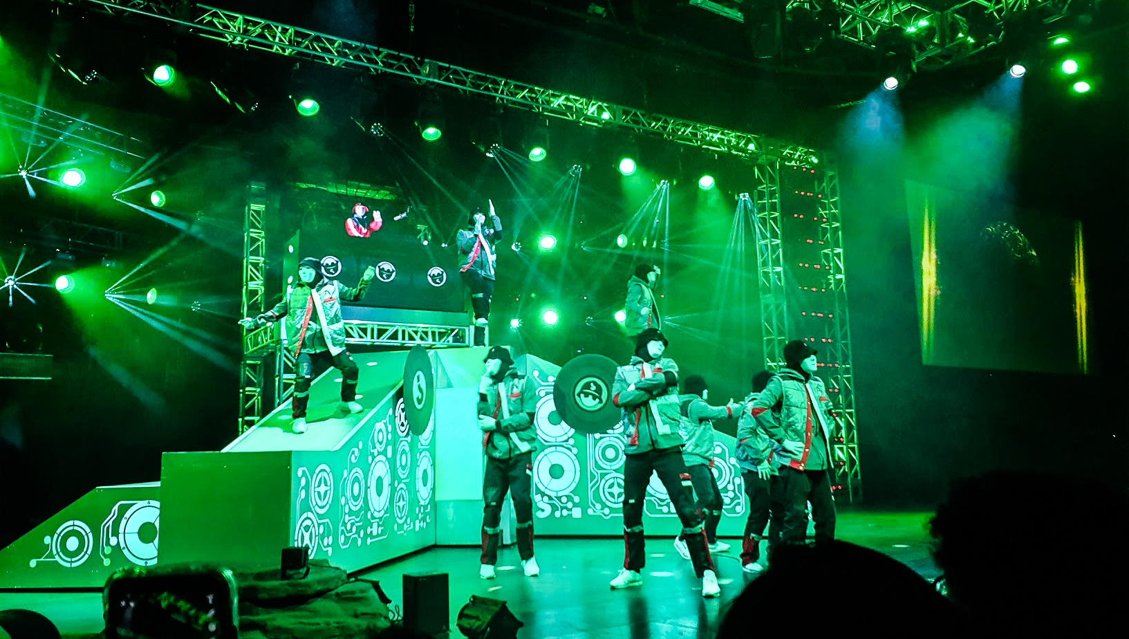 The whole crew is on stage, lit in bright green and the DJ rocks out