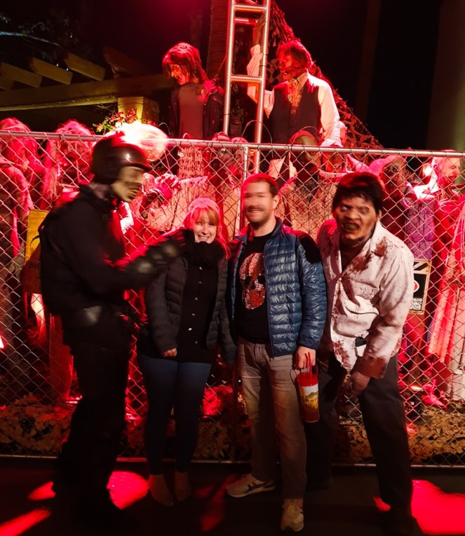 A blurry picture of Rosie and Karl grimacing with two Walking Dead zombies. It is clearly awkward