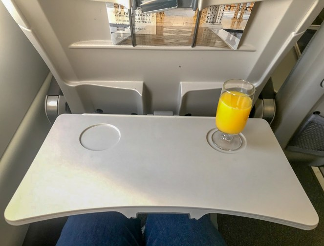 A plane tray table with a glass of orange juice on an airBaltic A220-300