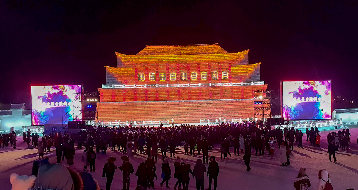 ice sculpture of traditional Chinese architecture, lit in red and oragne with a large screen either side at Harbin Ice and Snow World