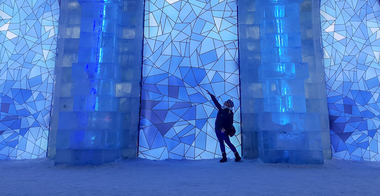 Rosie standing against blue stained glass ice building at Harbin Ice and Snow World