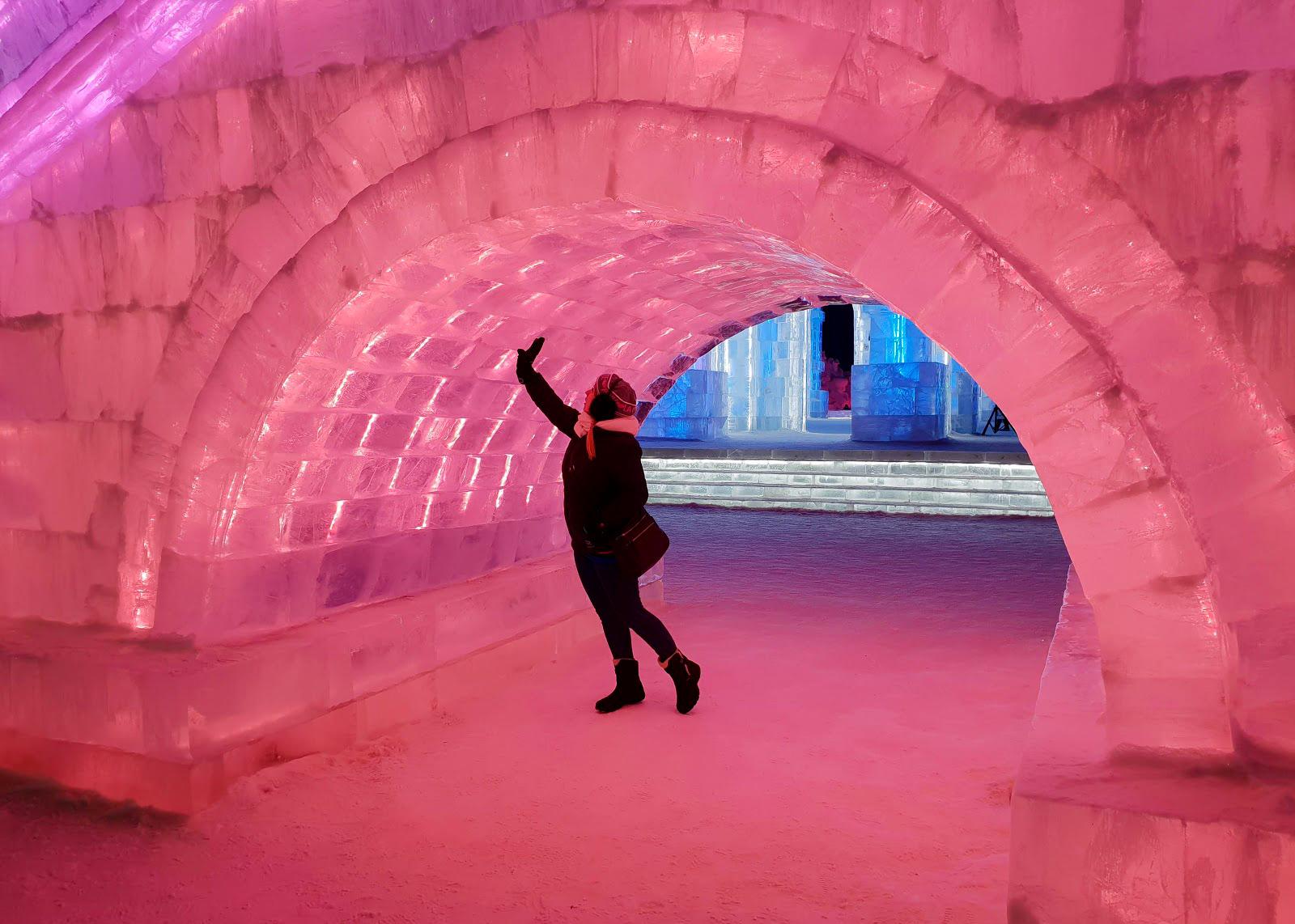 Rosie standing under an ice bridge lit in pink at Harbin Ice and Snow World