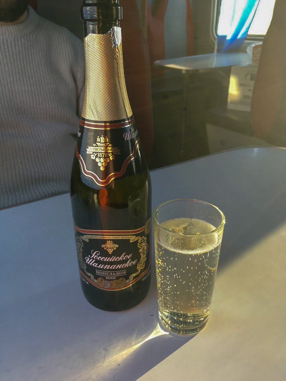 A bottle and glass of Champansky on a table of a Trans-Siberian Train