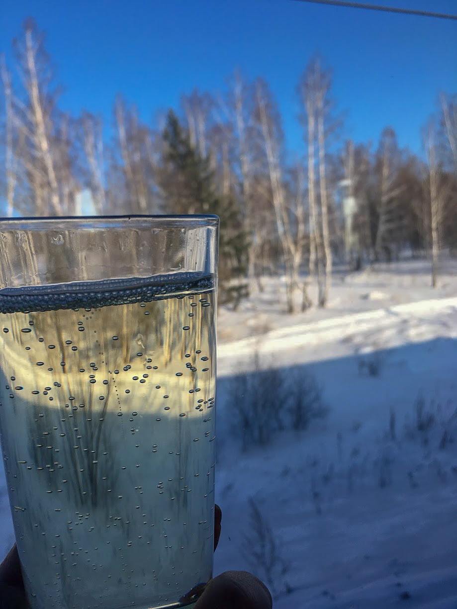 A glass of Champansky against the window of a Trans-Siberian Train