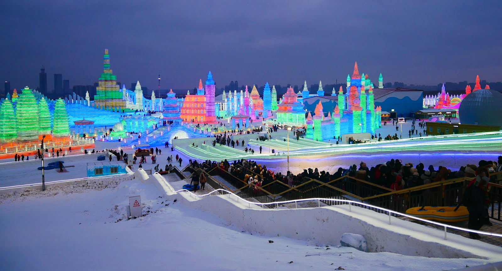 ice buildings and slide at night at Harbin Ice and Snow World