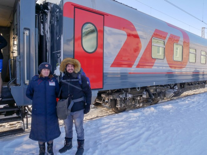 Karl with his backpack poses next to the Provoditsa of our Trans-Siberian Train