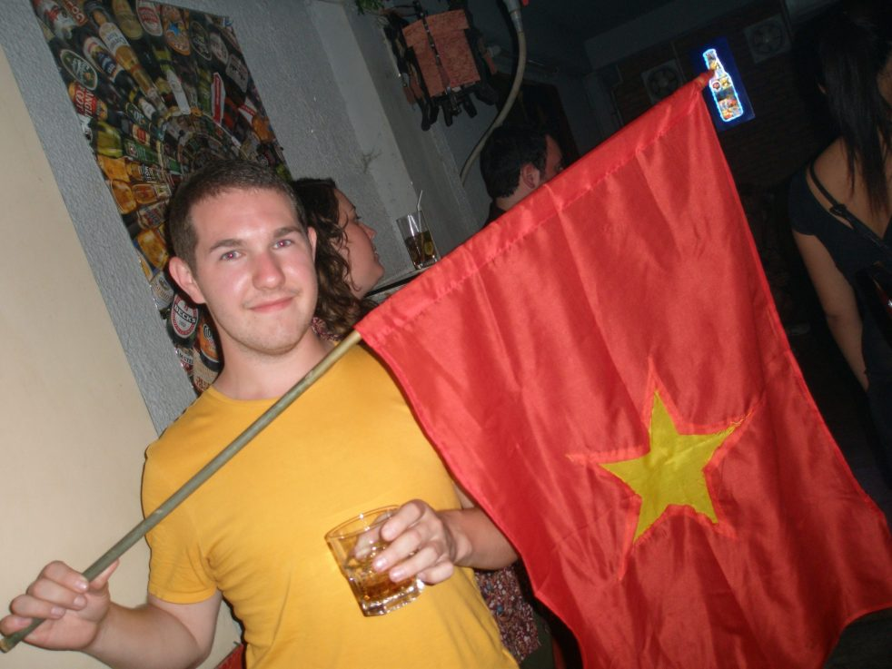 Karl in a yellow t-shirt holding a Vietnamese flag