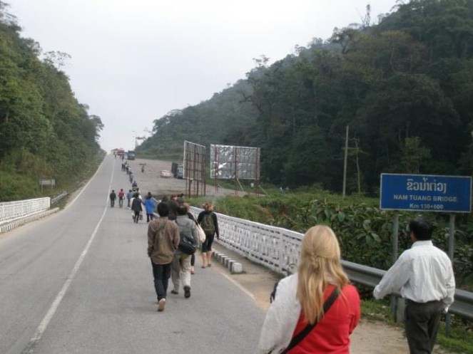 People walk along the road towards the Vietnamese border at the Nam Tuang Bridge