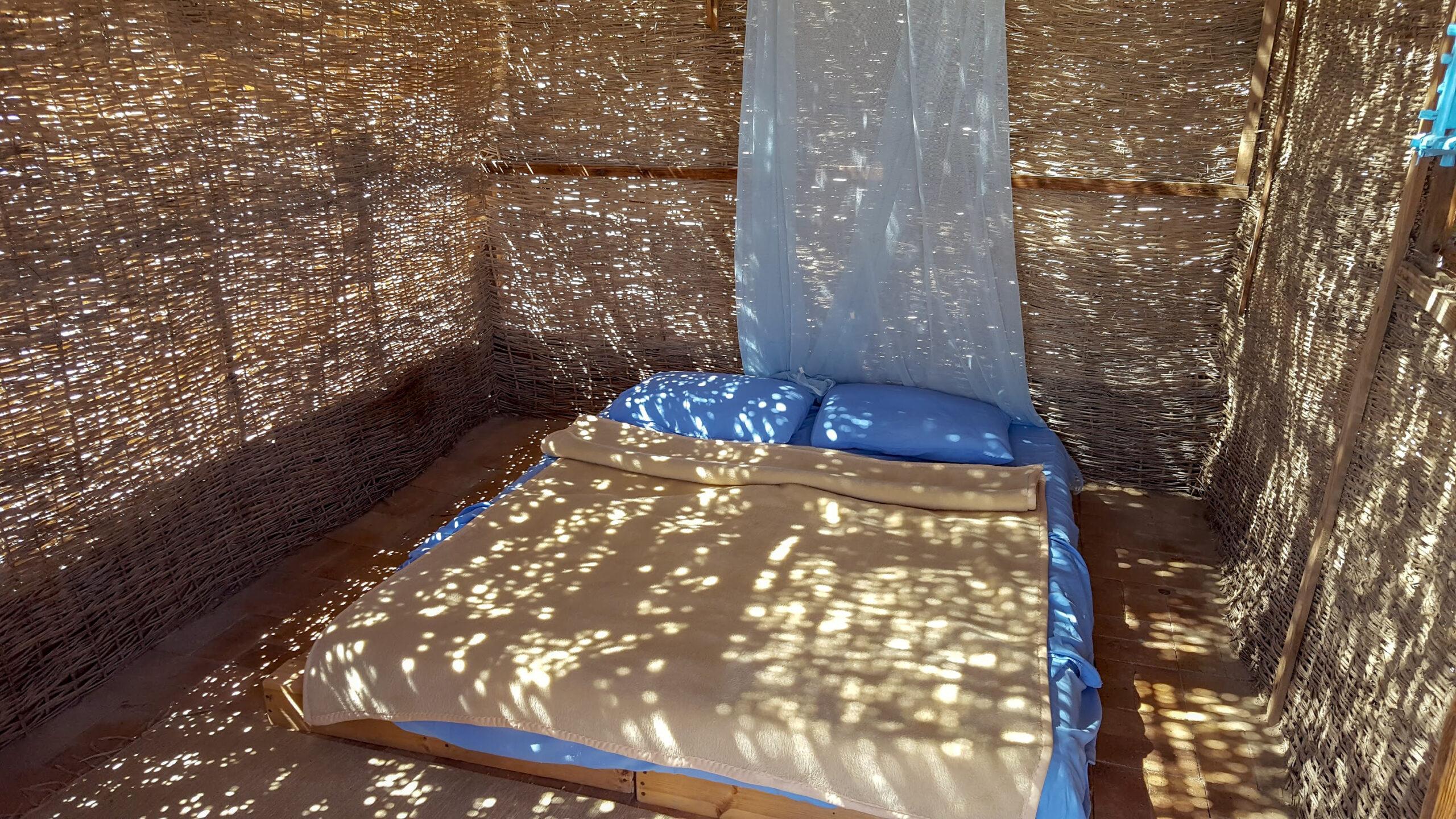 Inside a sun dappled Husha Hut with a blue bed, Aqua Sun, Gulf of Aqaba, Egypt