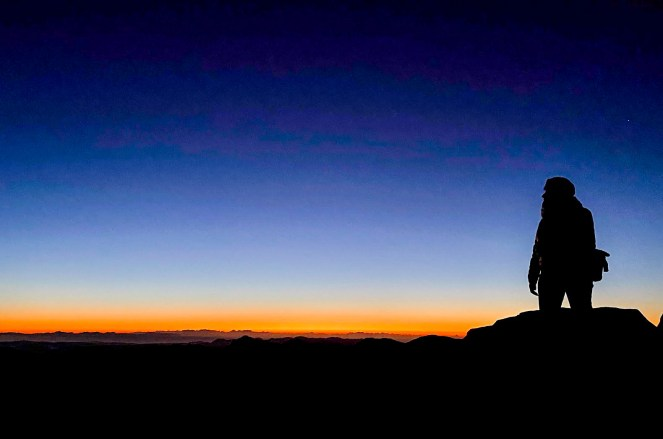 The silhouette of a walker against the sunrise at the summit of Mount Sinai, Egypt