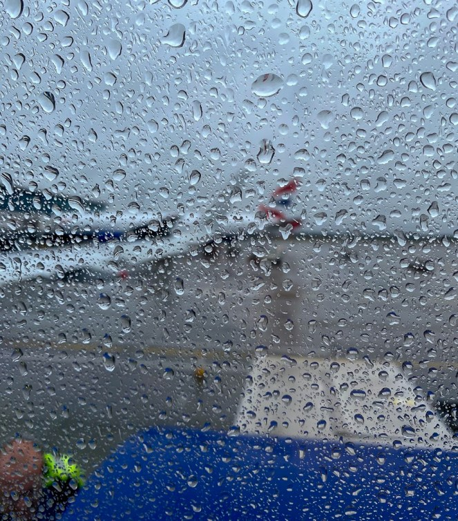 view out of a British Airways plane window covered in rain of the wing