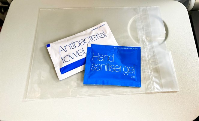 Antibacterial towel and hand sanitser gel packets on a British Airways plane tray table