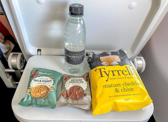 a small Harrogate water bottle, Tyrells mature cheddar & chive crisps, Belgian chocolate and oat & honey biscuits on a plane tray table