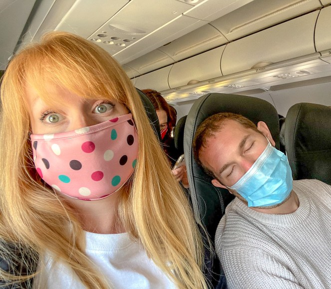 Rosie on a plane wearing a pink spotty face mask sitting next to Karl who is asleep wearing a surgical face mask