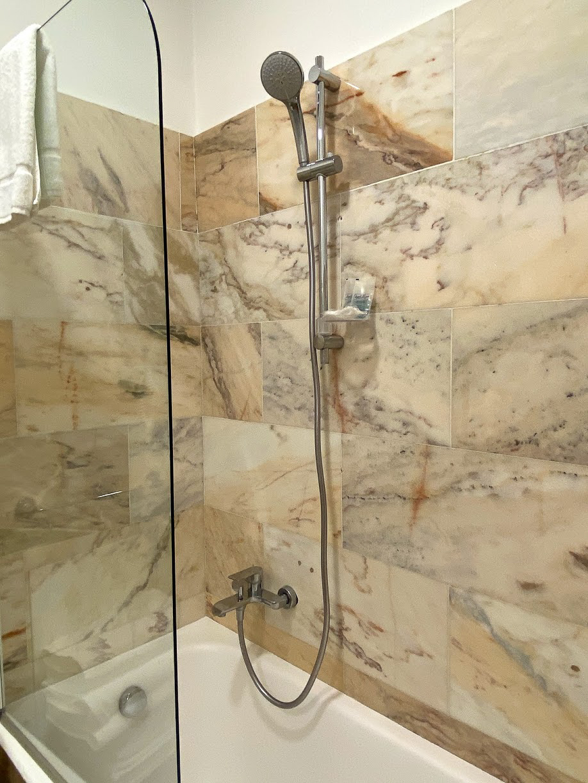 A shower over a bathtub with marble effect tiling at Atlantis Inn B&B Castel Gandolfo, Italy
