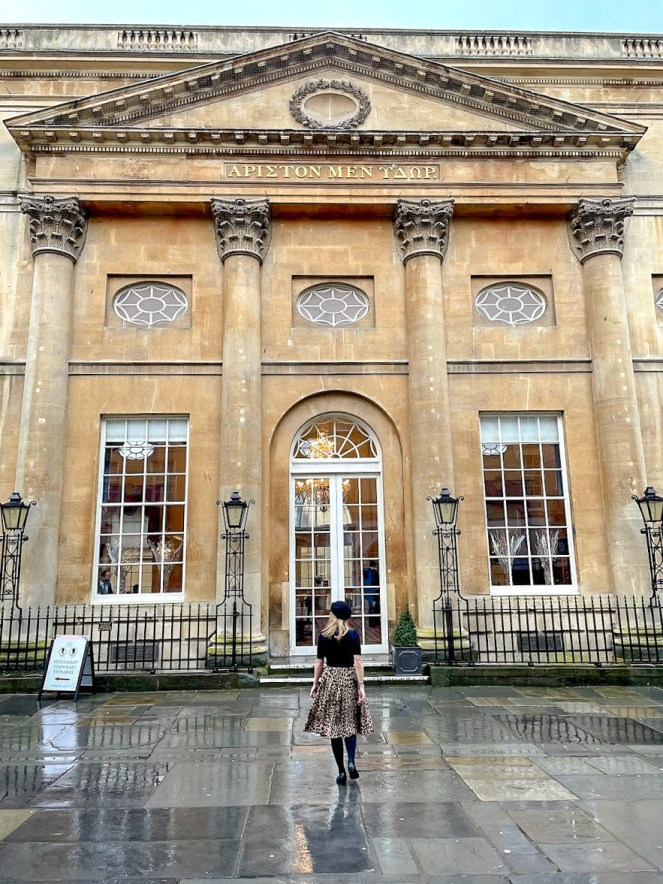 Rosie outside The Pump Room Bath, built with limestone and 4 corinthian columns