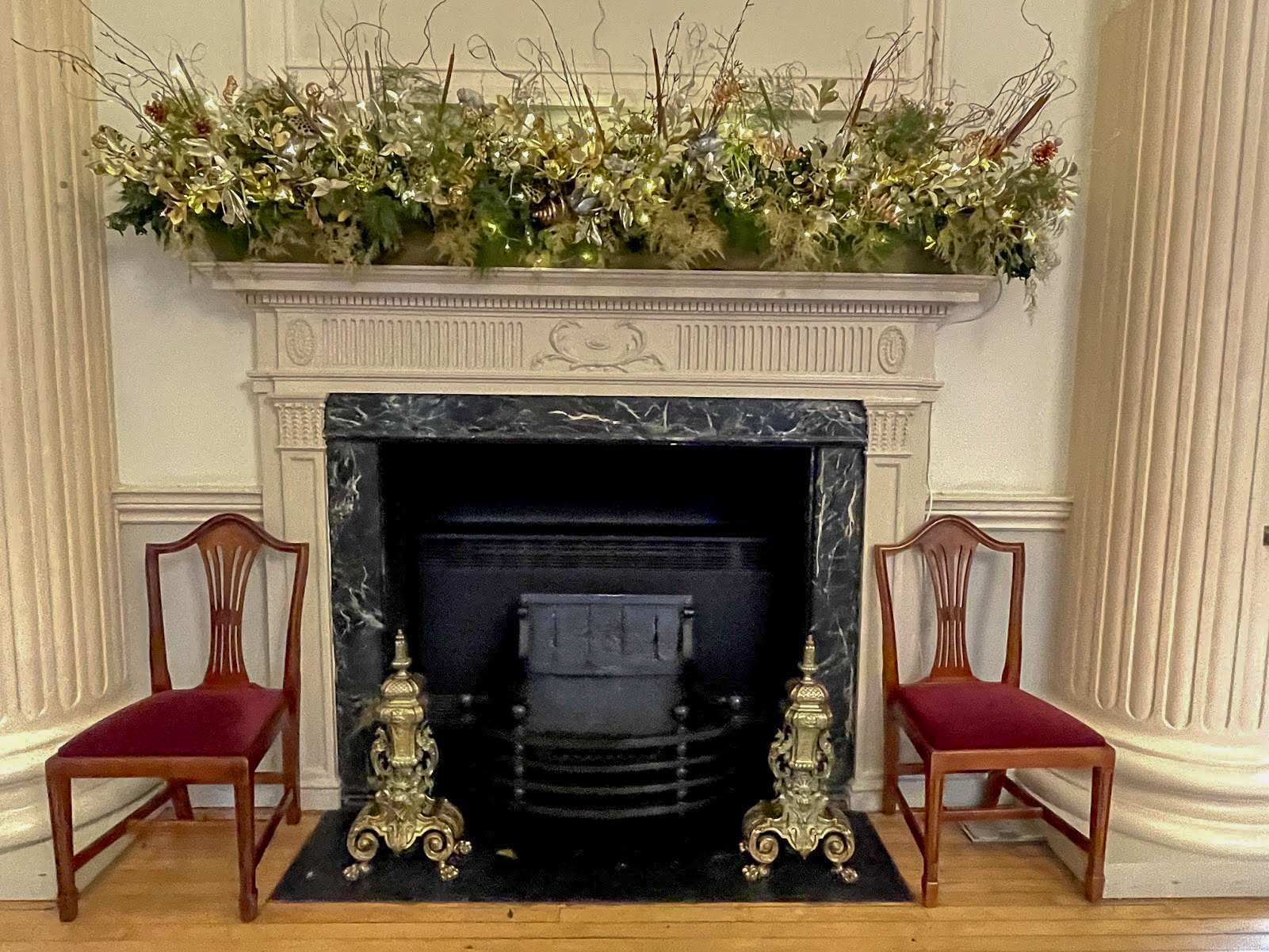 A black fireplace with Christmas decorations on the marble surround in The Pump Room Bath