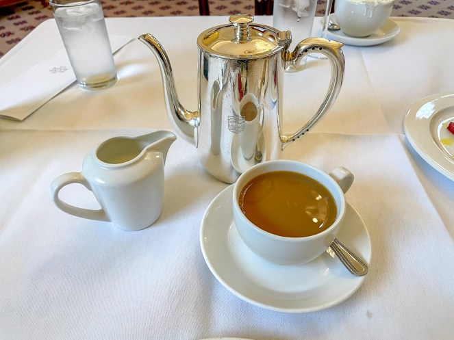 a silver coffee pot, a cup and a small jug of milk on a white table cloth in The Pump Room Bath