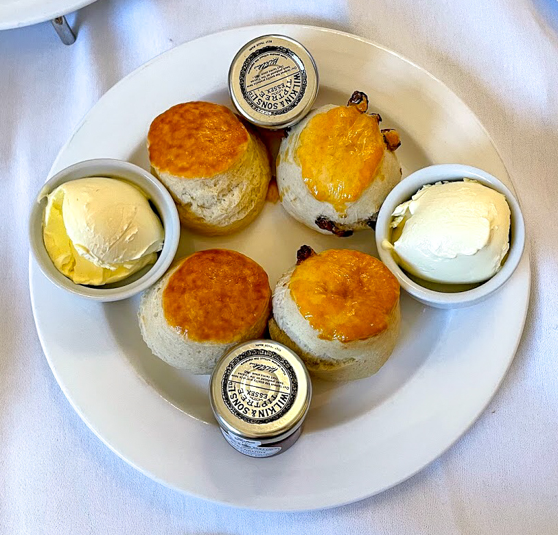 2 plain and 2 fruit scones, 2 pots of Dorset clotted cream and 2 small jars of Wilkin & Sons strawberry jam on a plate at The Pump Room Bath