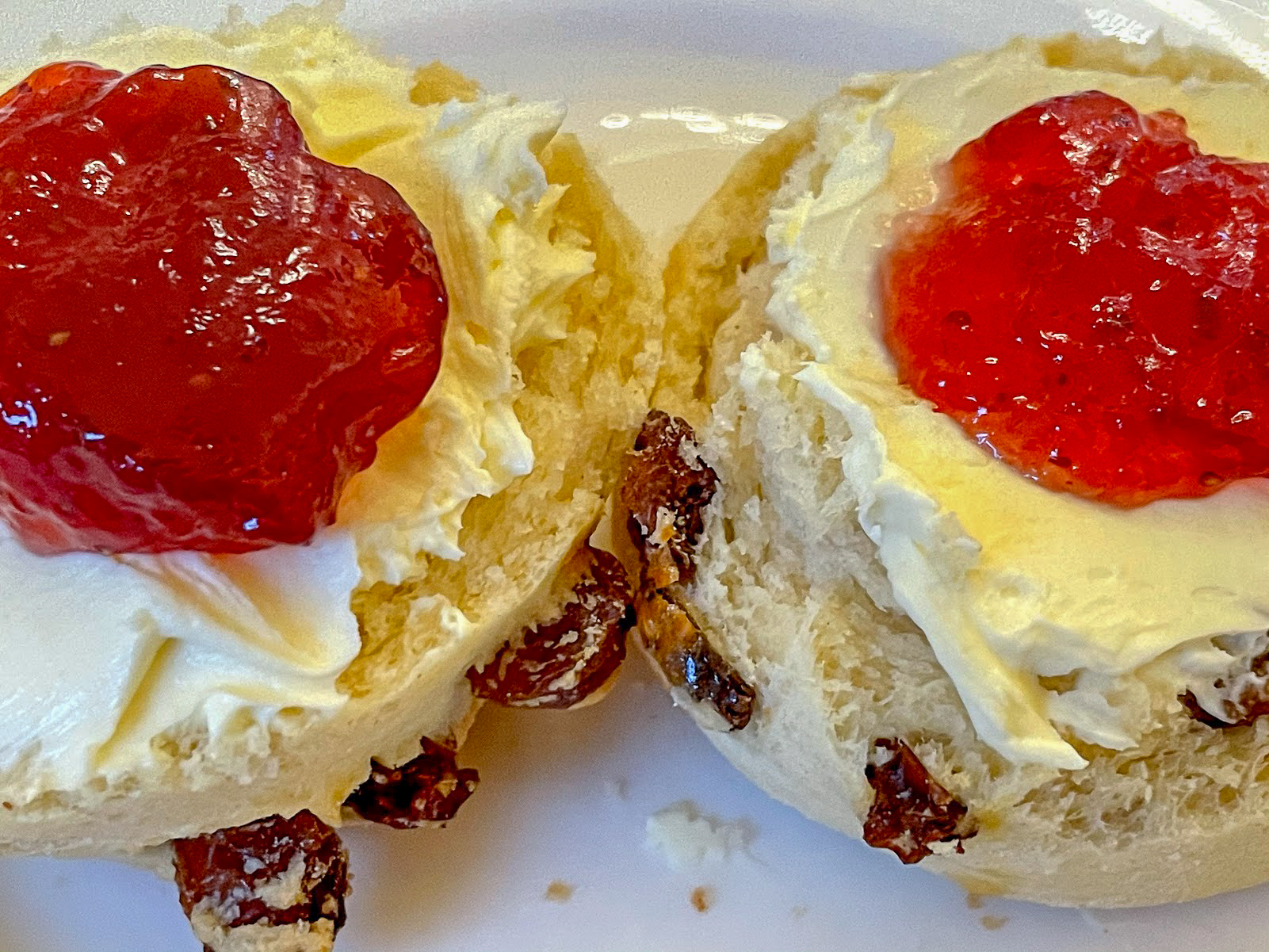 close up of a scone with Dorset clotted cream, topped with strawberry jam